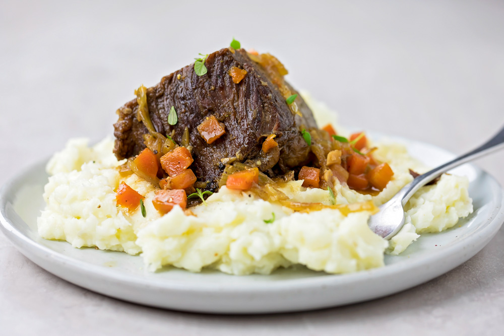 Instant pot short ribs on plate with mashed potatoes