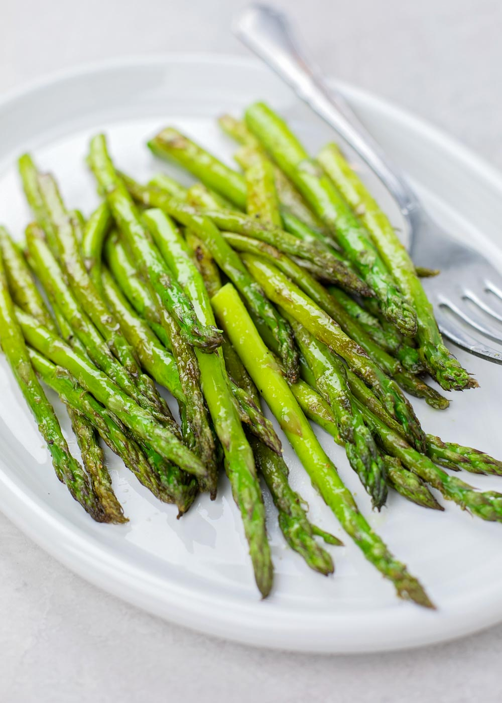 Roasted asparagus recipe on white plate