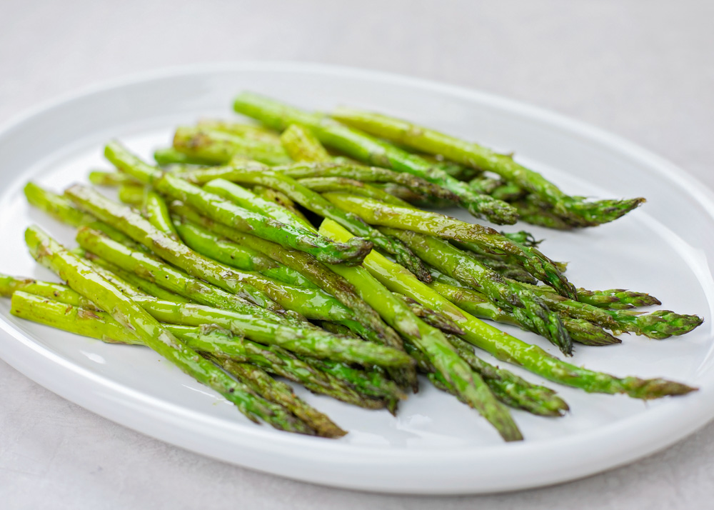 Oven roasted asparagus on white plate