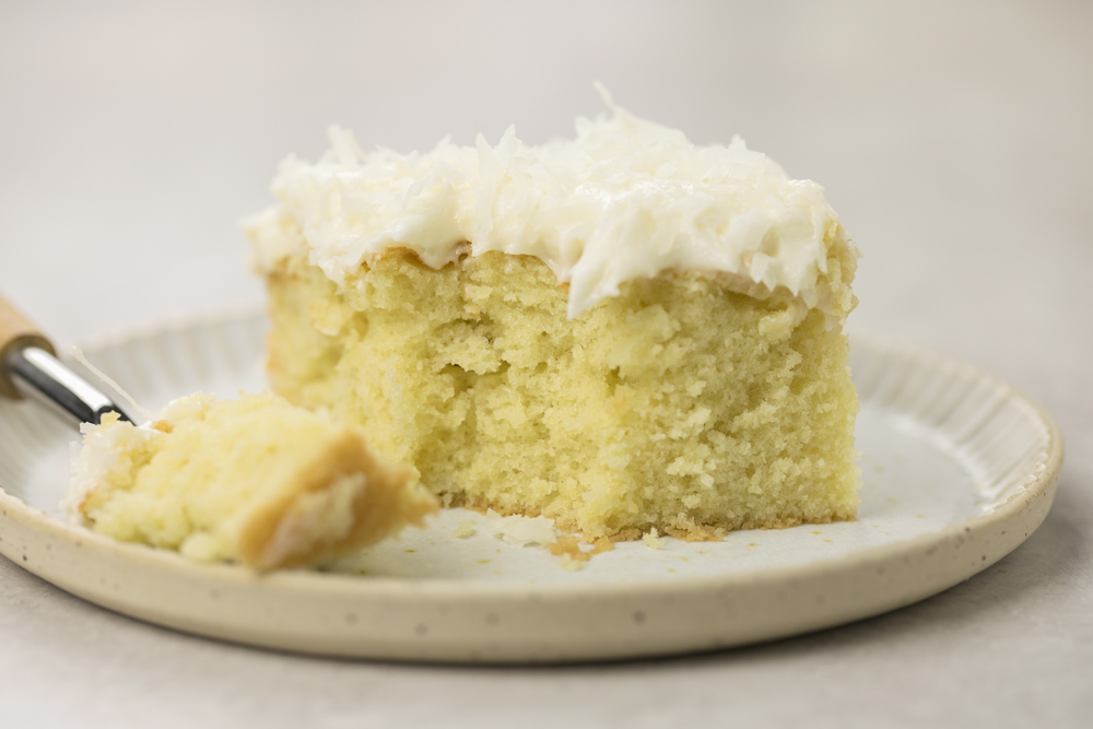 A slice of coconut cake on a white plate