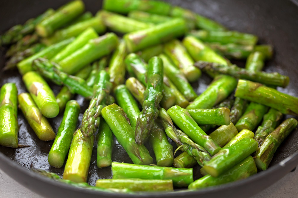 Asparagus being sautéed in a skillet