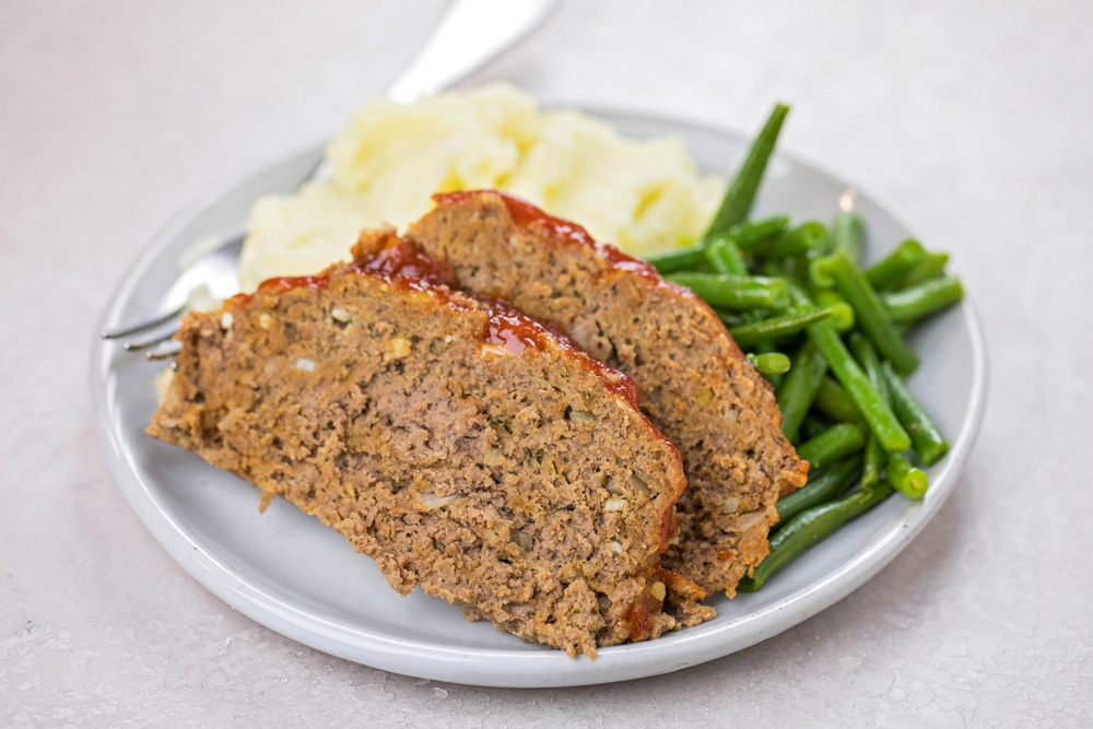 Instant pot meatloaf on a plate with mashed potatoes and green beans