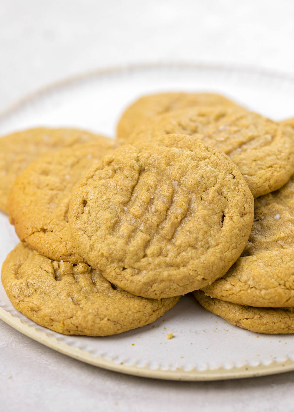 Close up of Easy Peanut Butter Cookies stacked on a white plate