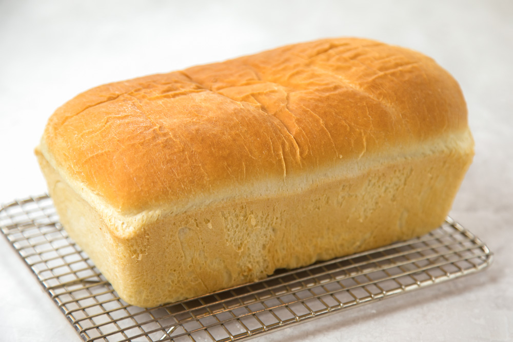 A loaf of homemade white bread on a cooling rack
