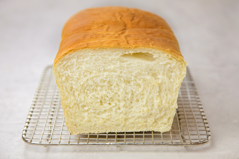 White bread loaf on a cooling rack
