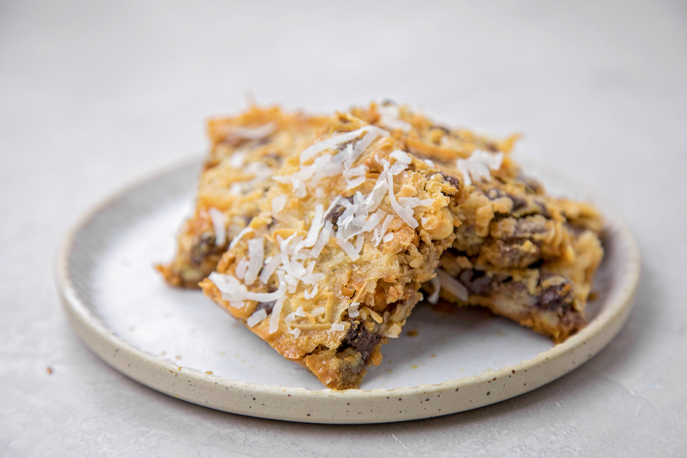 A stack of 7 layer bars on a white plate