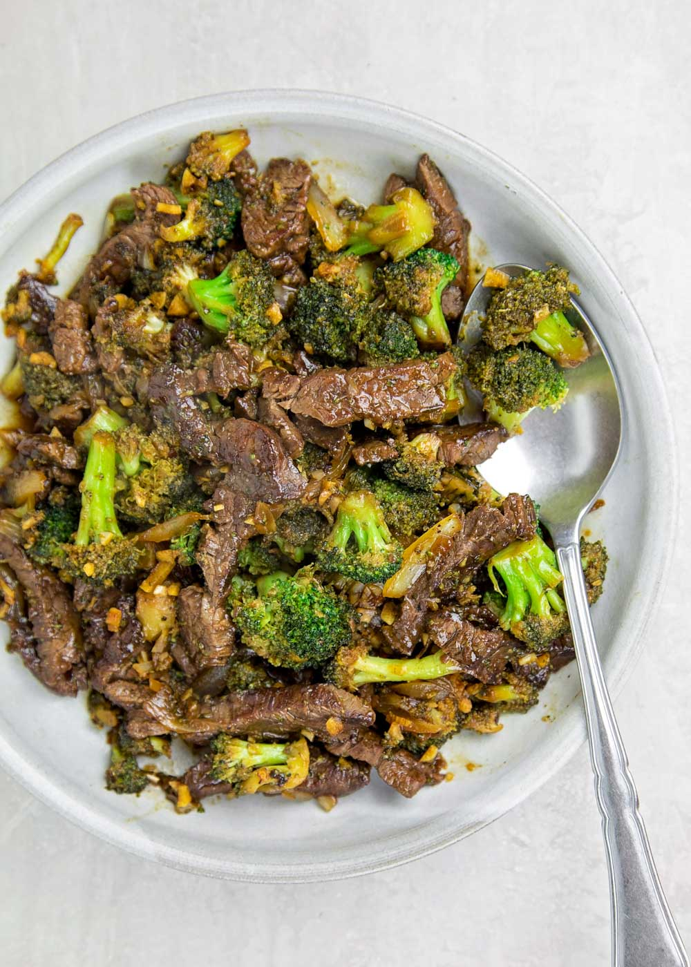 Beef and broccoli stir fry on a white plate with a spoon