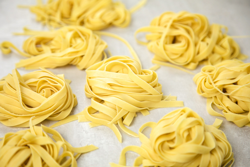 Bundles of homemade pasta on parchment paper