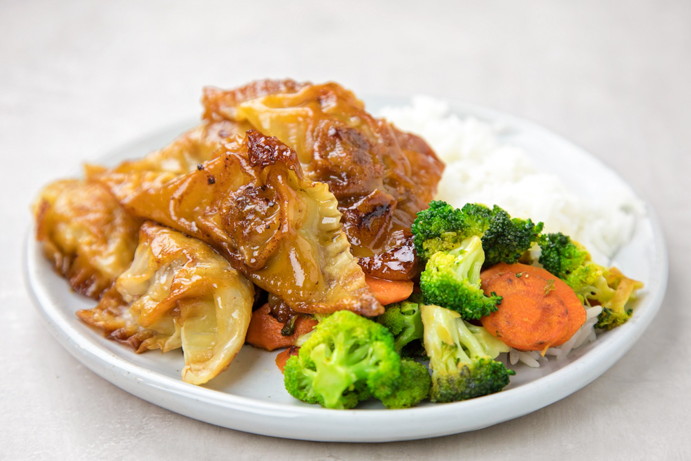Potstickers on a plate with rice and veggies