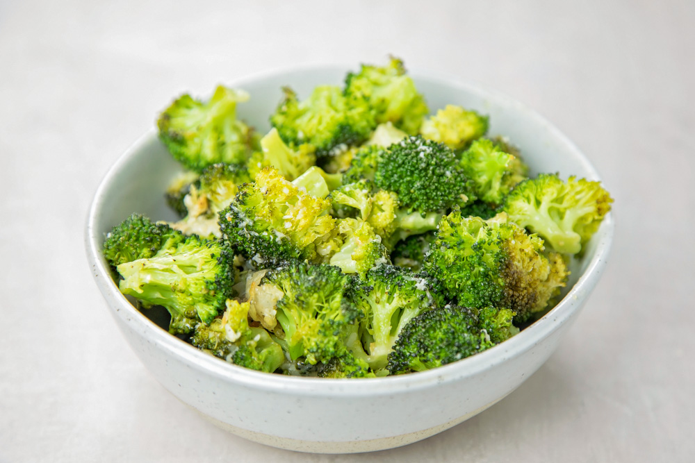 Oven roasted broccoli in a white bowl