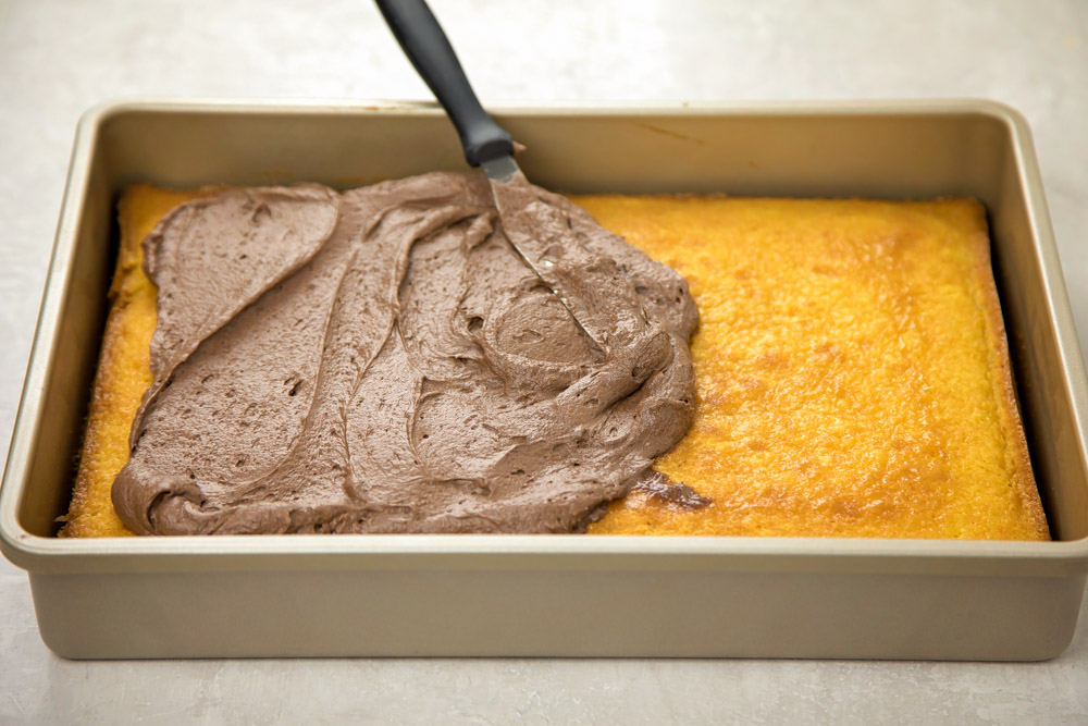 Spreading chocolate frosting onto homemade yellow cake