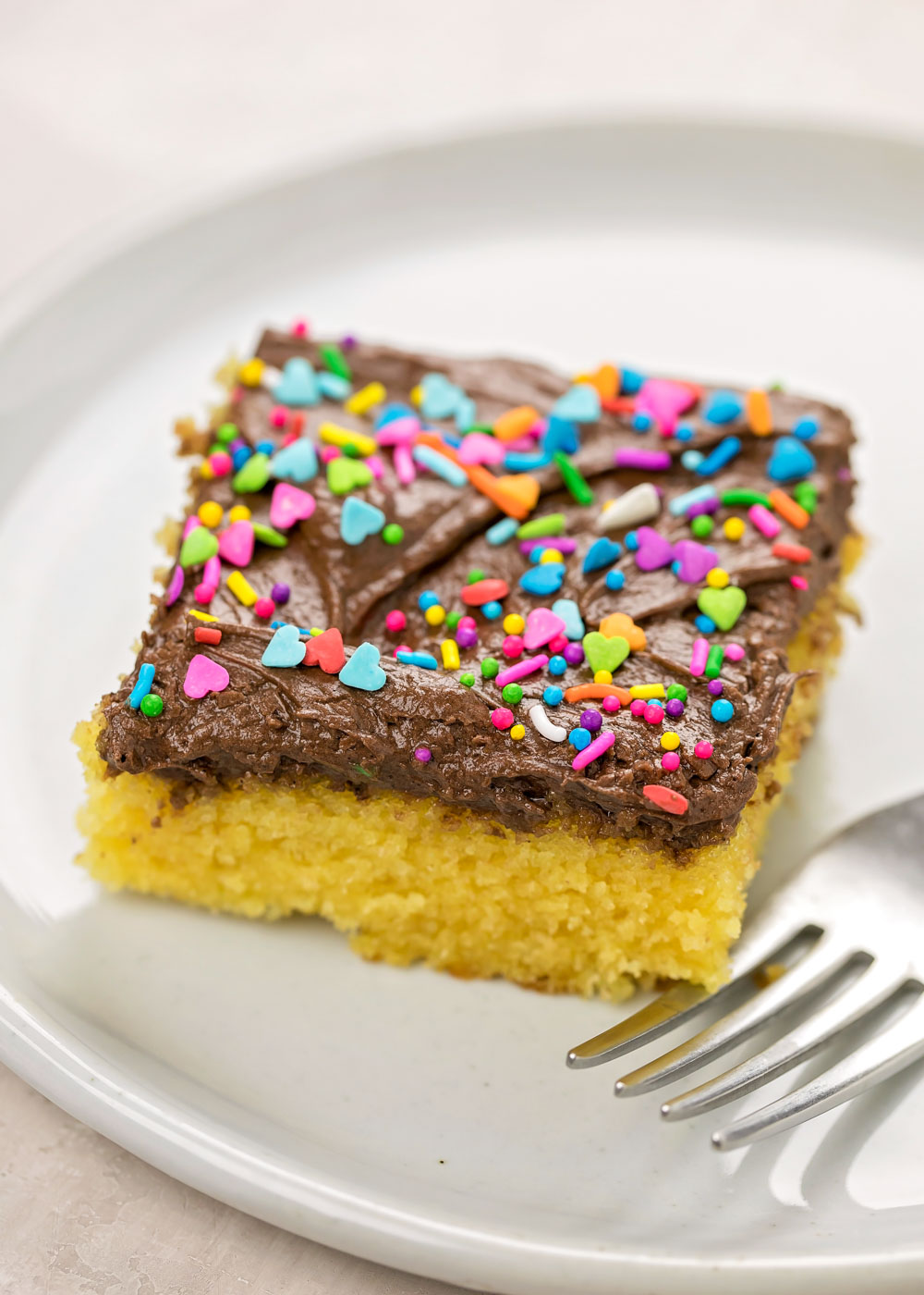 A slice of moist yellow cake with chocolate frosting on a white plate