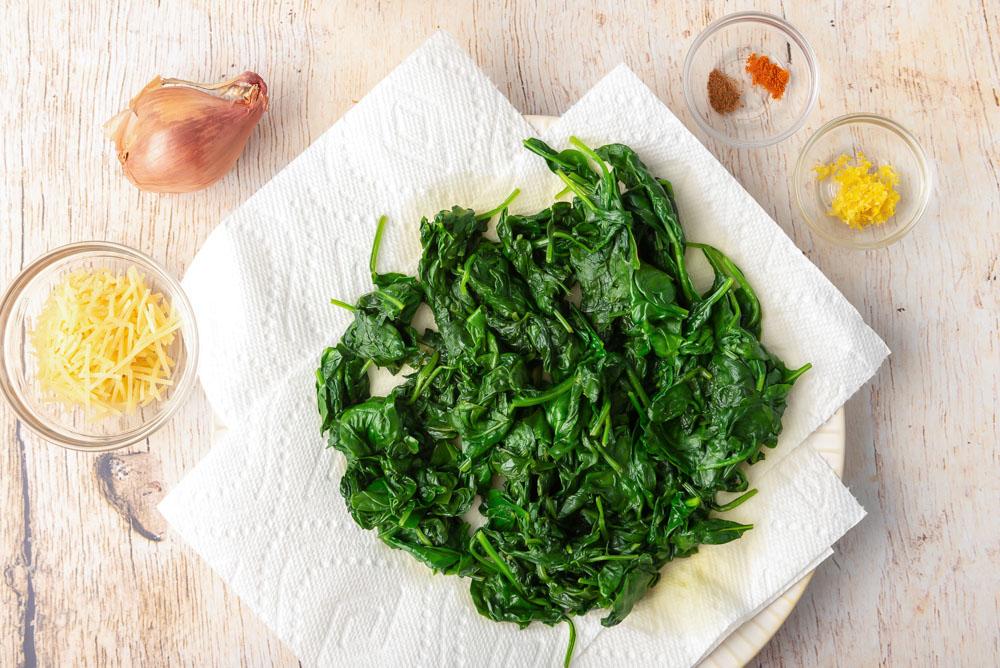 Espinacas marchitas y otros ingredientes para la receta de espinacas a la crema