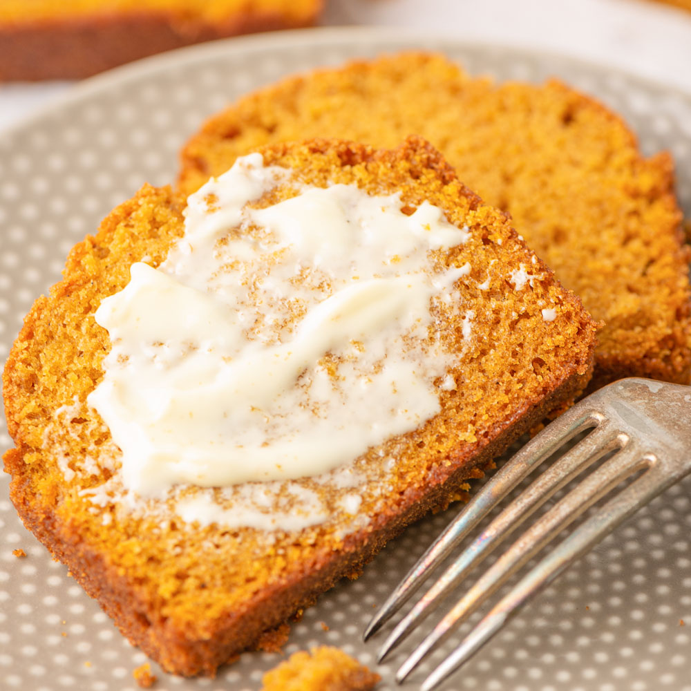 Two slices of pumpkin bread lathered with butter