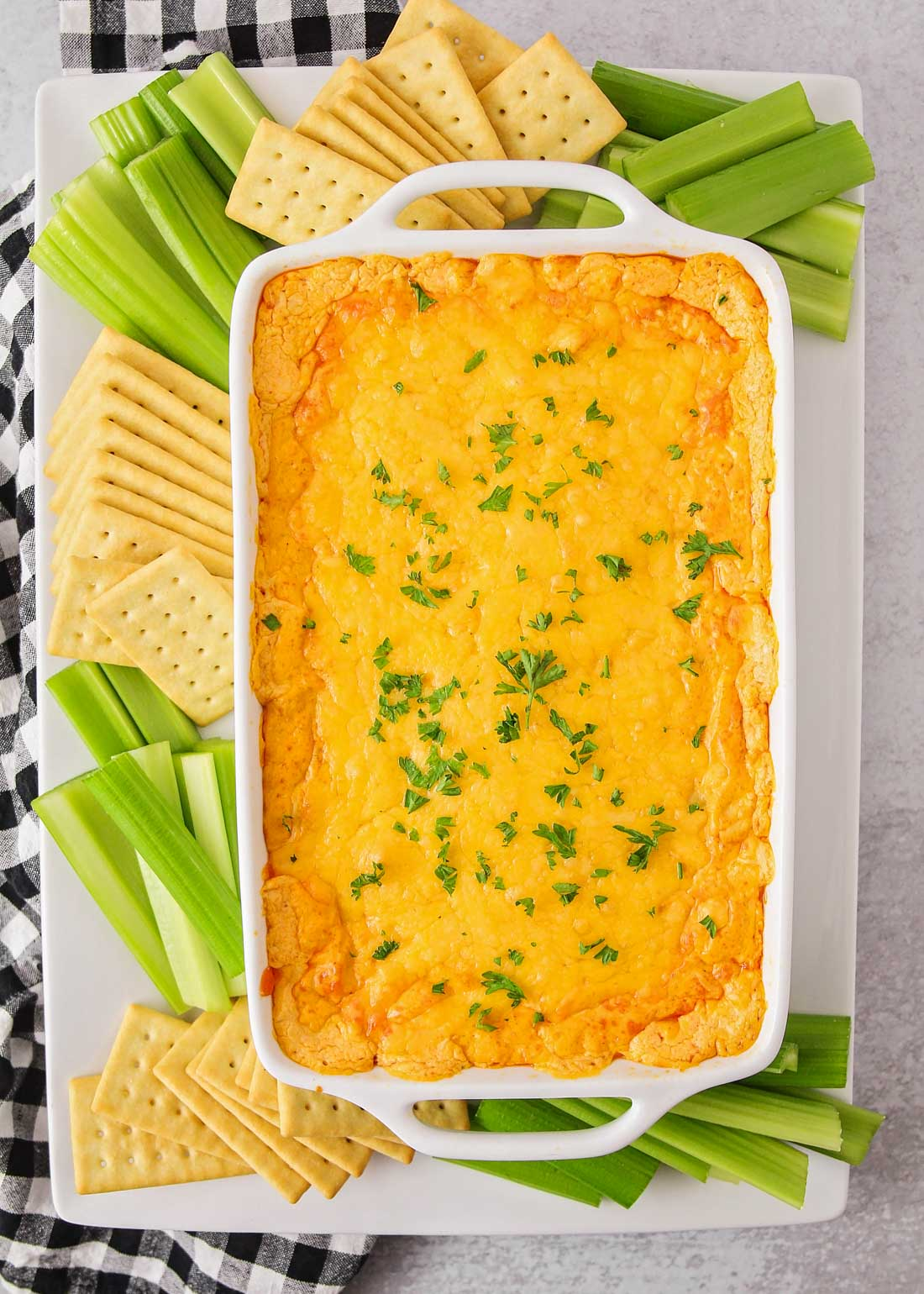 Easy buffalo chicken dip recipe on a platter with celery and crackers