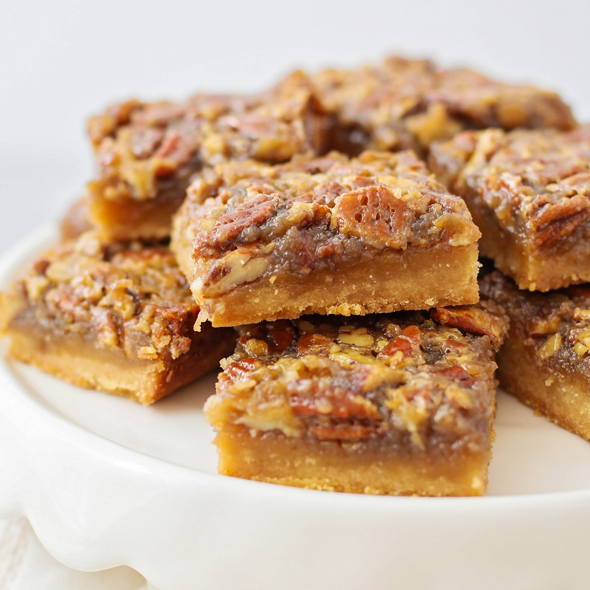 Pecan pie bars stacked on a white dessert stand