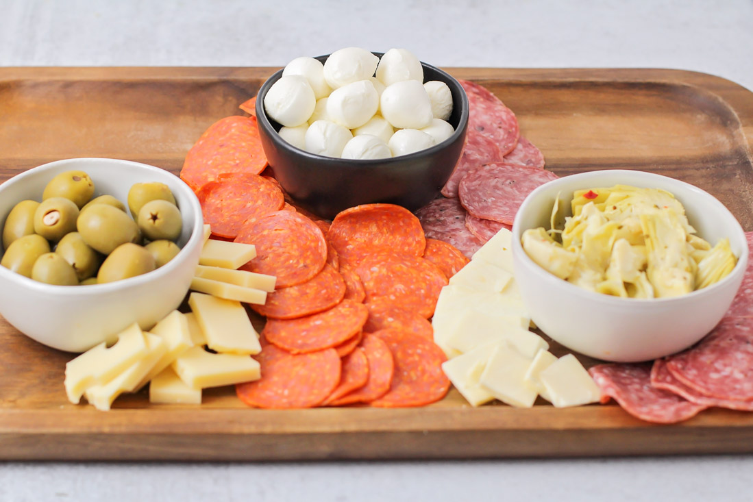 Layering meats and cheeses on antipasto platter