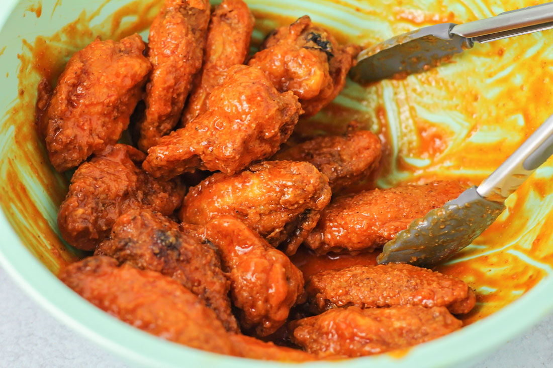 Coating wings in hot wing sauce