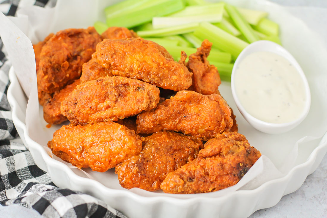 Hot wings in a serving dish with celery sticks and ranch