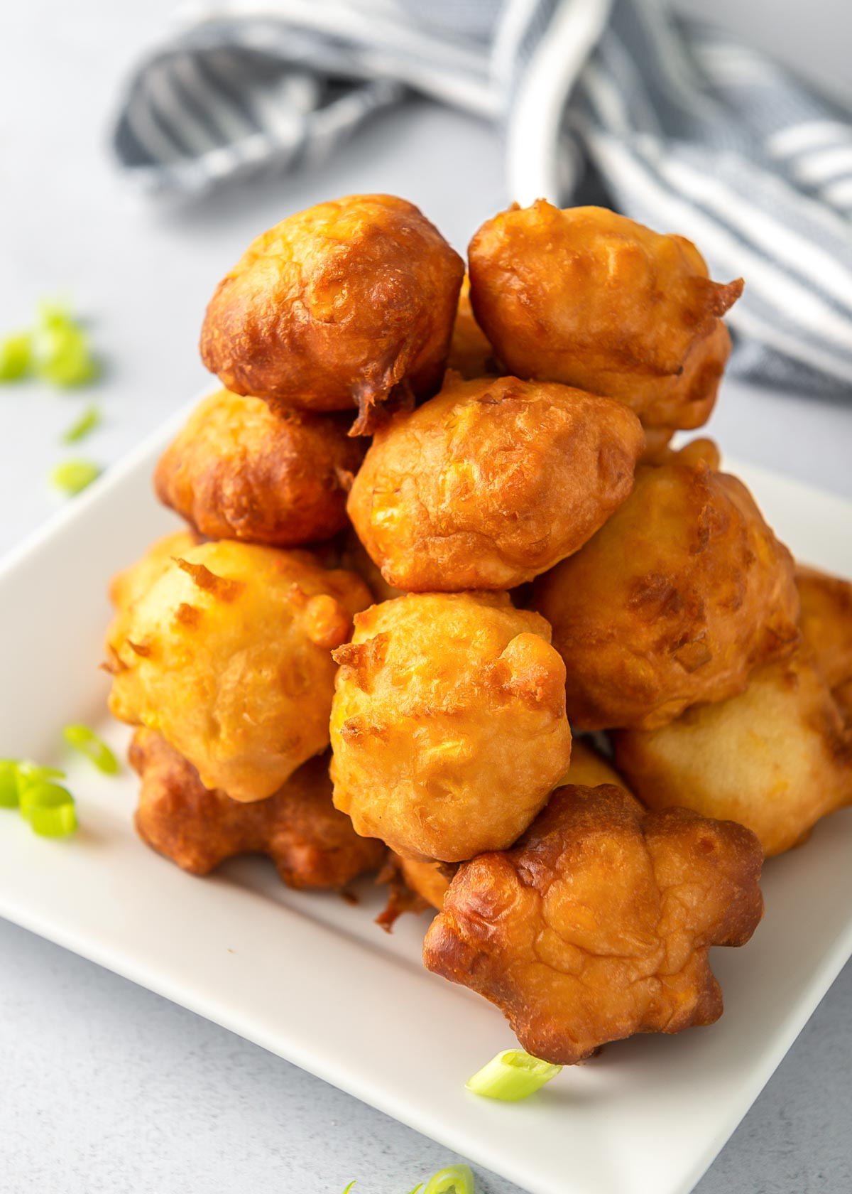 Homemade corn fritters stacked on a white plate