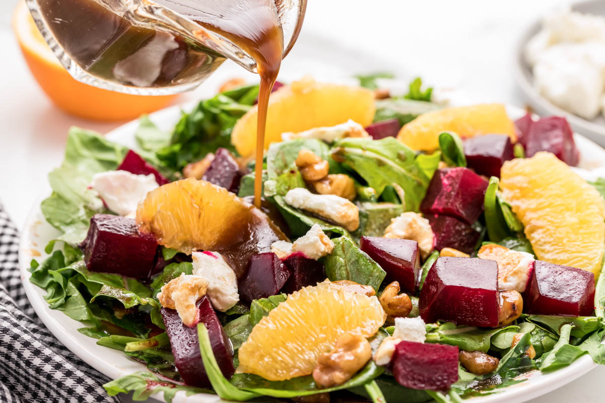 Pouring dressing over roasted beet salad