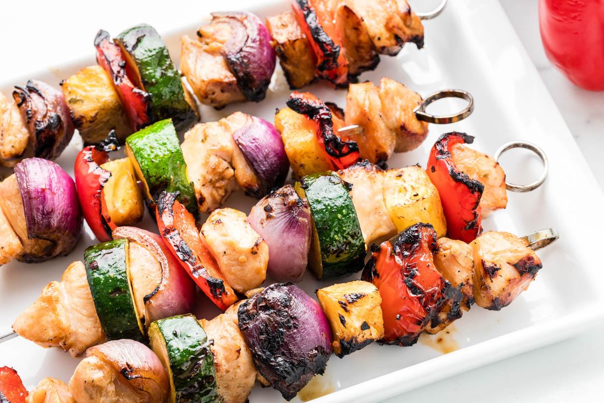 Chicken kabobs on a white serving platter
