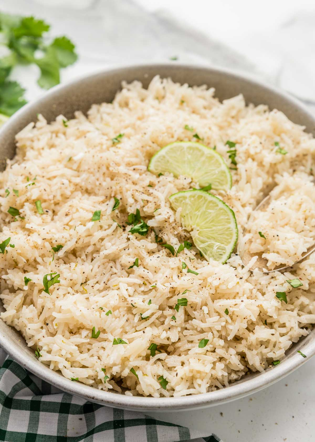 Close up of coconut lime rice in a bowl with two lime slices