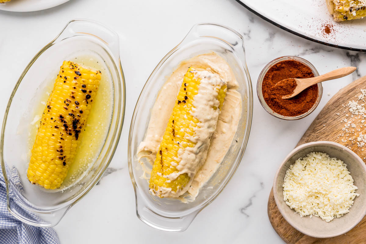 Covering mexican corn on the cob with cream sauce, cheese, and seasoning
