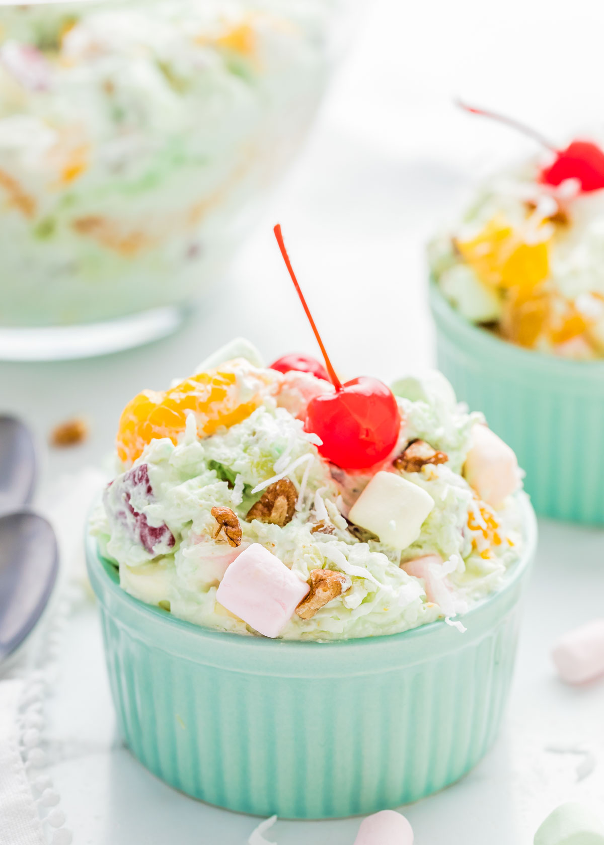 Ambrosia fruit salad in a dish, topped with a cherry