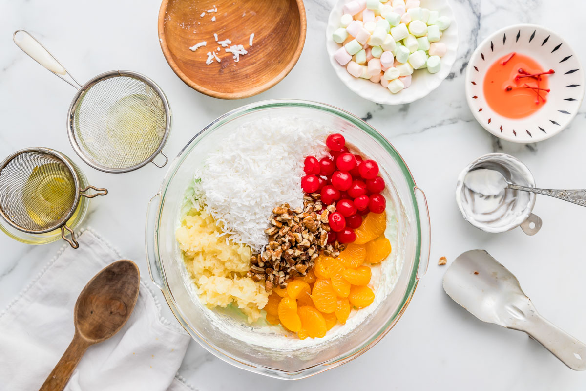 Combining ambrosia fruit salad ingredients in a mixing bowl