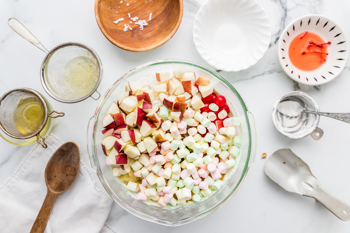Making ambrosia fruit salad in a glass mixing bowl