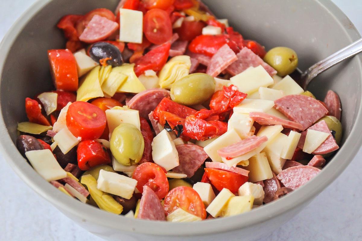 Combining antipasto salad ingredients in a bowl