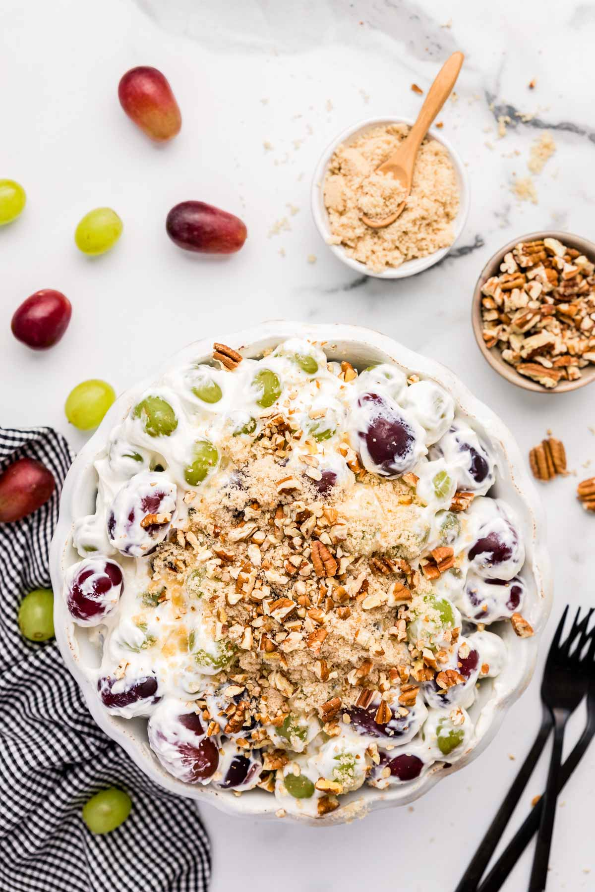 A bowl of grape salad with pecans