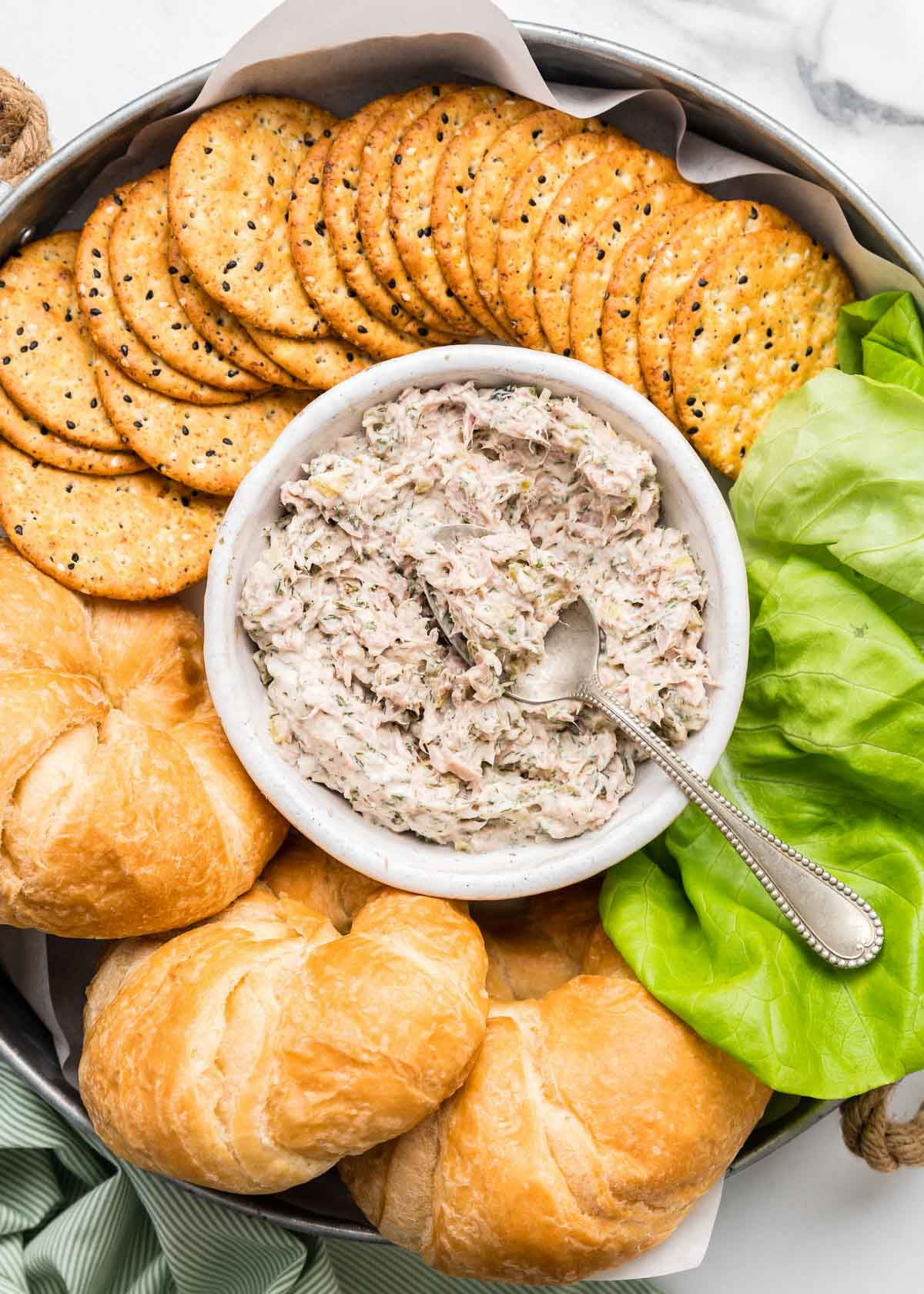Tuna salad in a small serving dish surrounded by crackers and croissants