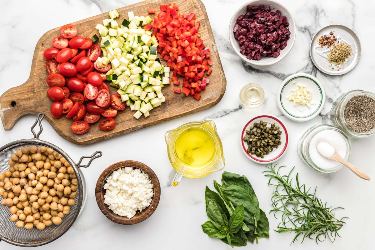 Ingredients to make chickpea salad recipe on a marble countertop