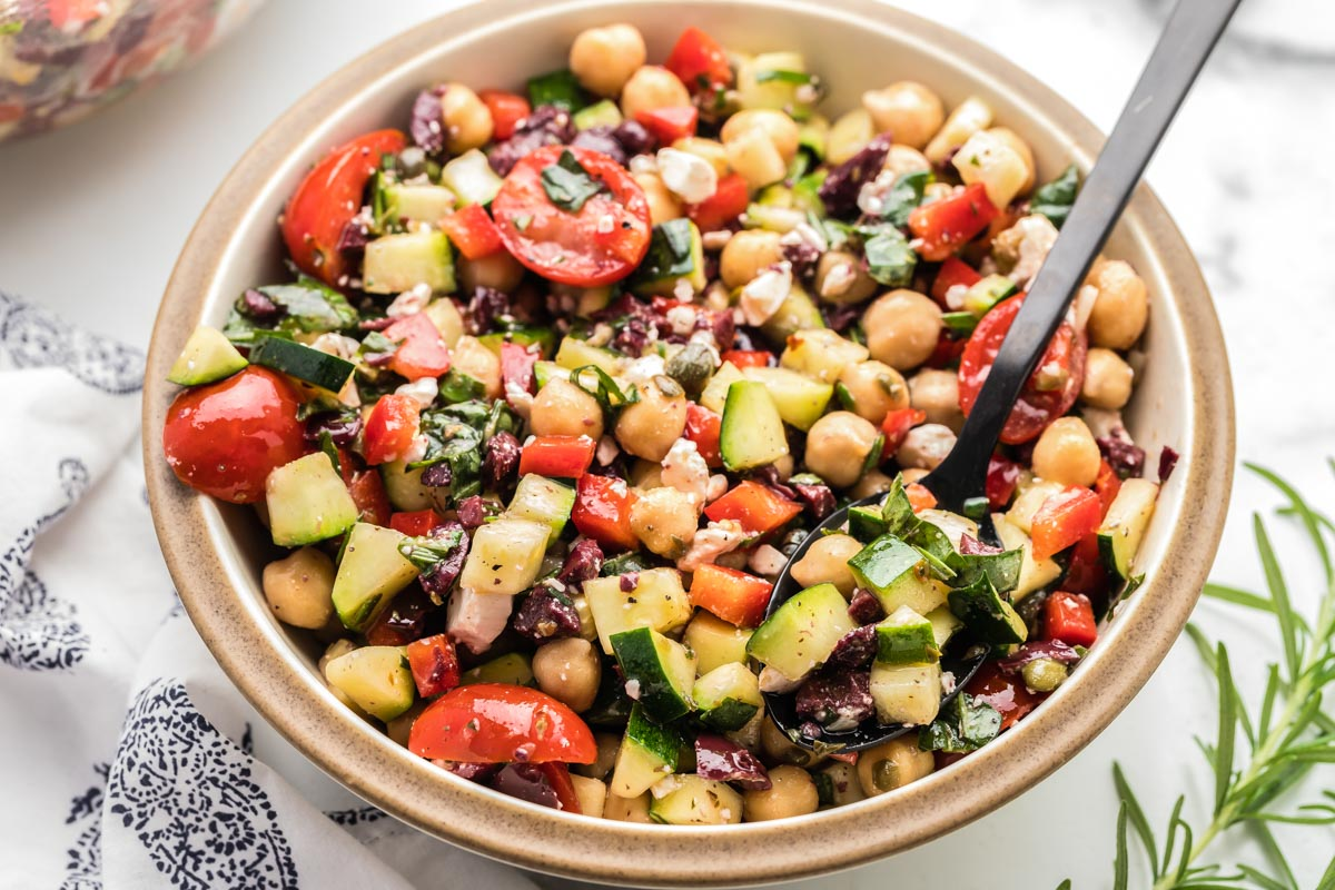 Chickpea salad in a bowl with a black spoon