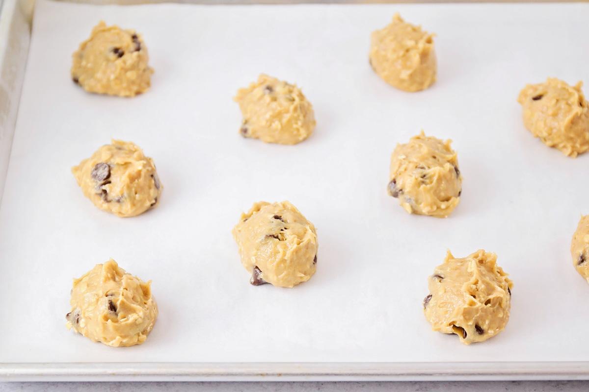 Balls of peanut butter banana oatmeal cookie dough on a baking sheet