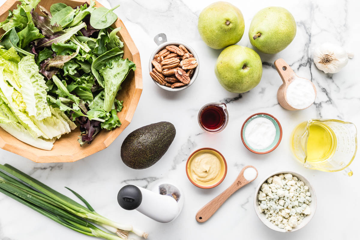 Ingredients for pear salad recipe sitting on a marble countertop