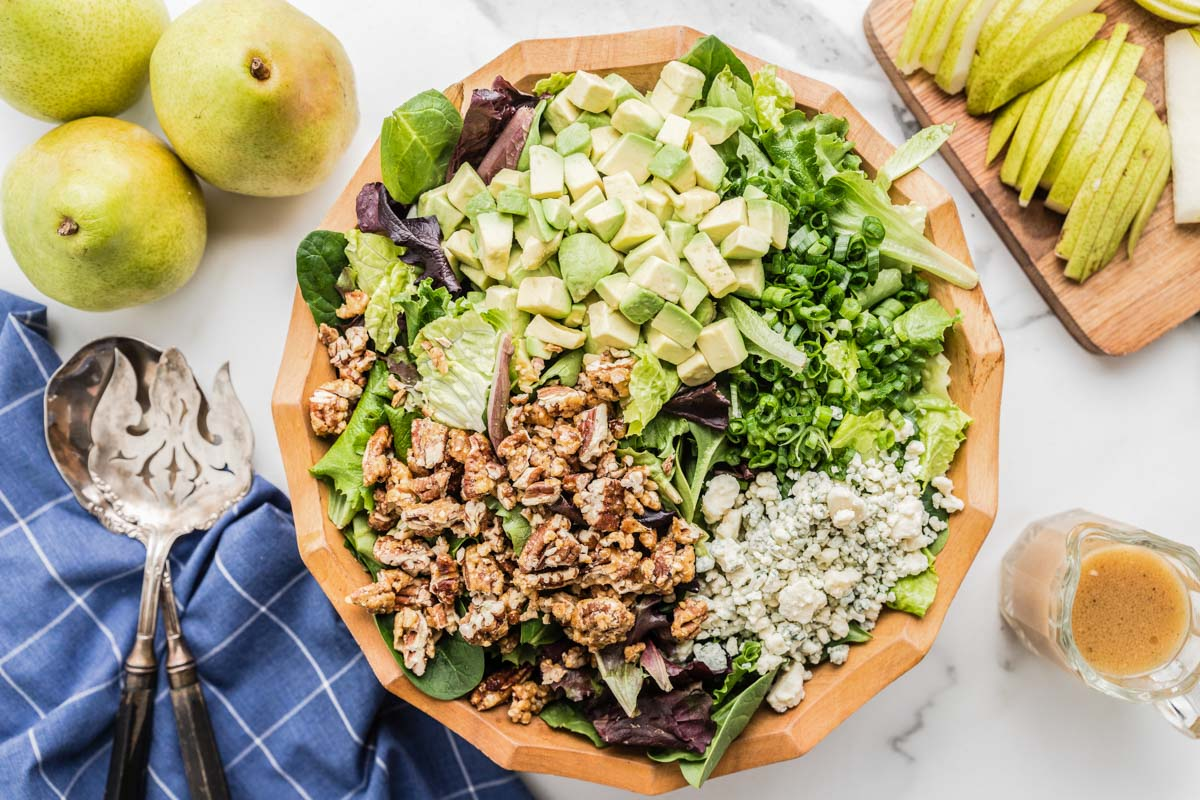 Pear salad in a decorative bowl with dressing on the side