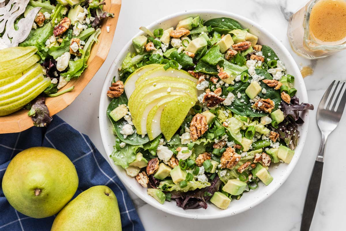 Pear salad topped with fresh pear slices in a white bowl