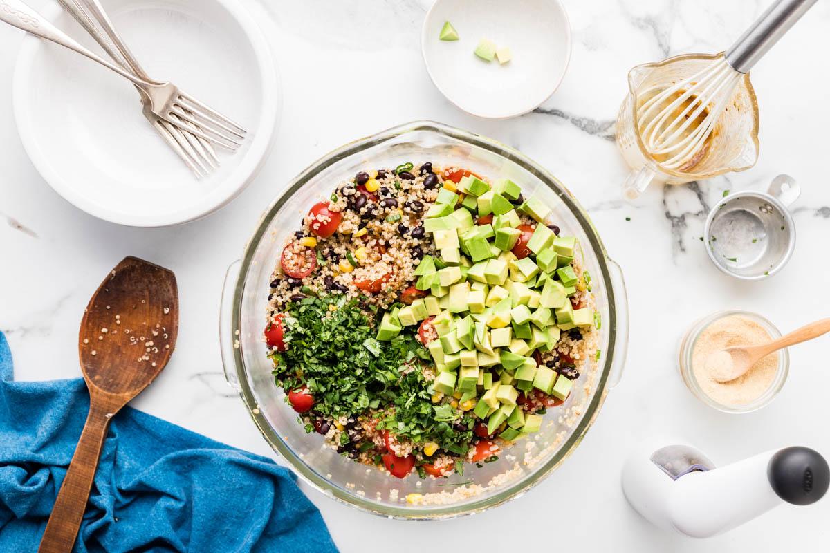 Adding avocado and cilantro to the bowl