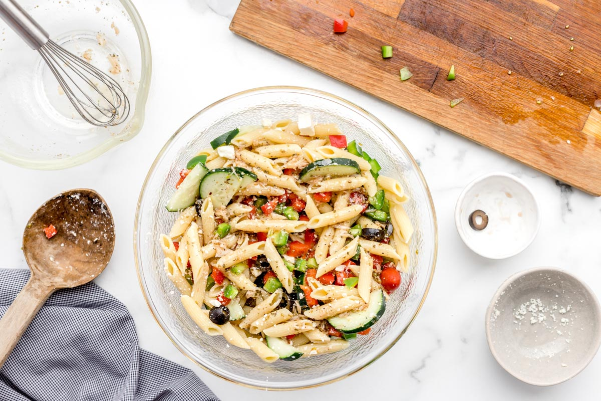 Mixed pasta salad topped with lemon vinaigrette in a glass bowl