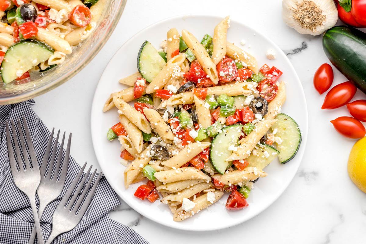 Greek pasta salad on a white dinner plate