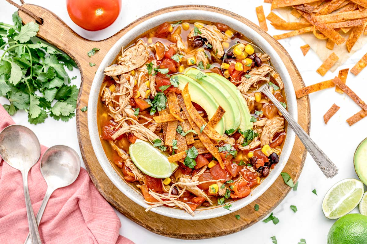 Instant pot chicken tortilla soup in a white bowl with a spoon