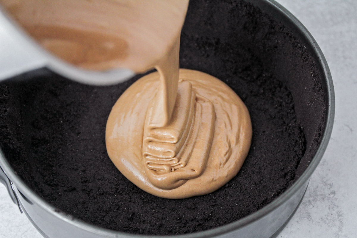 Pouring chocolate cake batter into the oreo crust