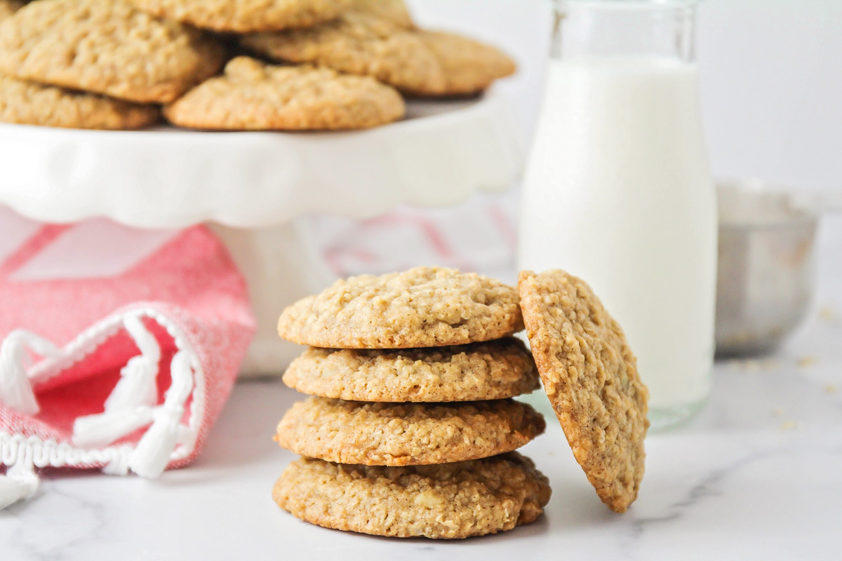 A stack of oatmeal cookies with a side of milk