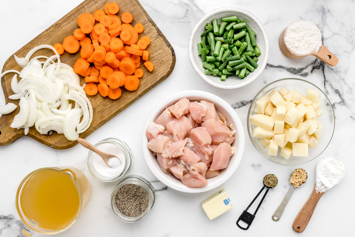 Ingredients for chicken stew recipe laid out on a marble countertop