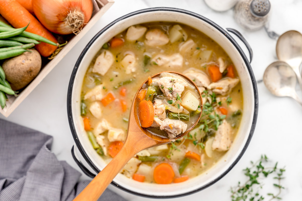 Chicken stew being scooped with a ladle