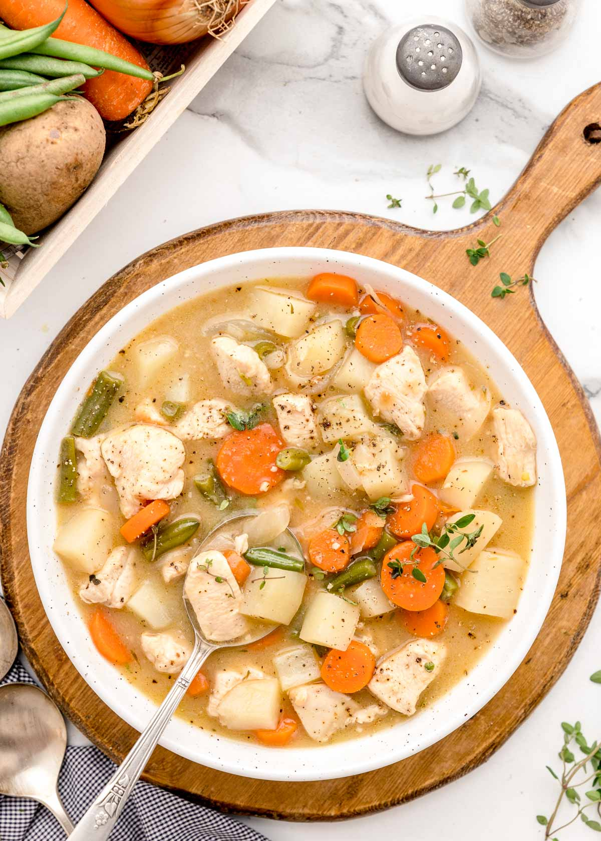 A white bowl full of chicken vegetable stew