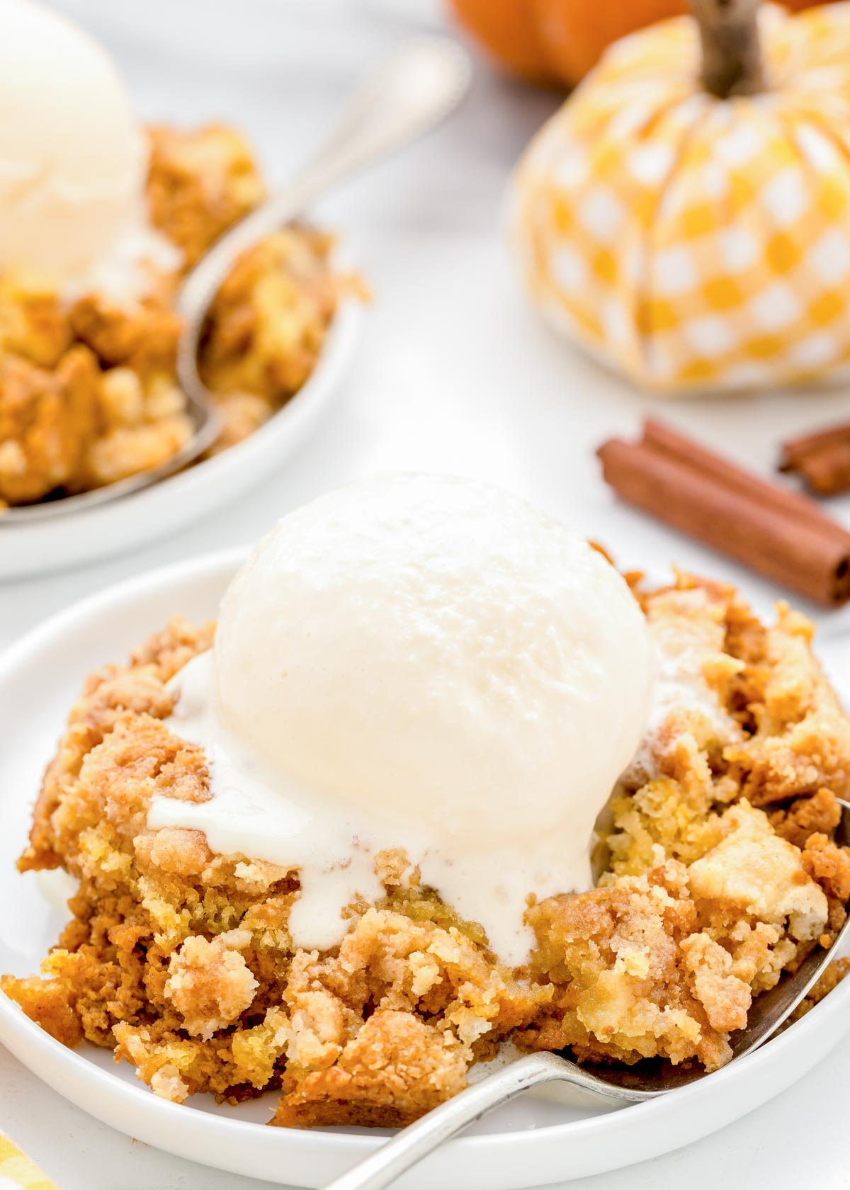 Pumpkin cobbler topped with vanilla ice cream on a white plate